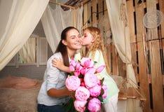 孩子祝贺母亲给花她的花束  免版税库存图片