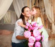 孩子祝贺母亲给花她的花束  免版税库存照片
