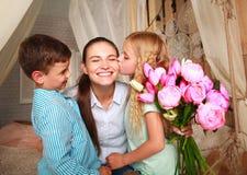 孩子祝贺母亲给花她的花束  库存照片