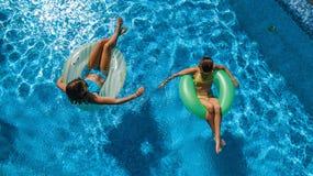 孩子空中顶视图从上面游泳池的,愉快的孩子在可膨胀的圆环油炸圈饼游泳并且获得乐趣在水中 图库摄影