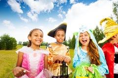孩子穿戴的佩带的万圣夜服装在公园 库存图片