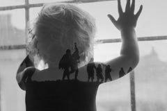 孩子站立在窗口和等待他的从战争的父亲 免版税图库摄影