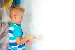 孩子绘有路辗的蓝色墙壁 男孩拿着一la 免版税库存照片