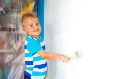 孩子绘有路辗的蓝色墙壁 男孩拿着一la 免版税库存图片