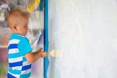 孩子绘有路辗的蓝色墙壁 男孩拿着一la 库存照片