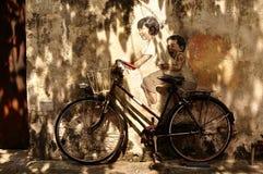 孩子绘画在周期的在街道上 免版税库存照片