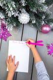 孩子给圣诞老人写信 孩子手 顶视图 免版税库存图片