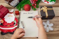 孩子给圣诞老人项目、儿童的手有笔的在木背景与装饰和圣诞礼物写一封信 免版税库存照片