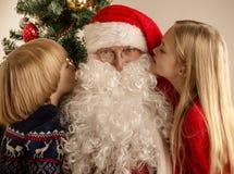 孩子耳语对圣诞老人 免版税库存照片