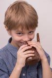 孩子舔从瓶子的巧克力釉 免版税库存照片
