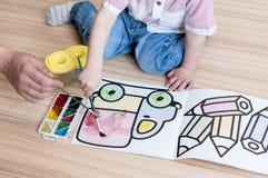 孩子花费与一张成人图画的时间与水彩 库存照片