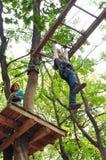 孩子获得乐趣在一个上升的冒险活动公园 免版税库存图片