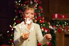 孩子获得乐趣在一次新年` s庆祝,拿着闪烁发光物 免版税库存图片