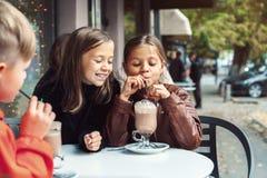 孩子获得乐趣在室外咖啡馆 库存照片
