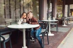 孩子获得乐趣在室外咖啡馆 免版税库存图片