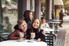 孩子获得乐趣在室外咖啡馆 免版税库存照片
