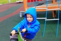孩子获得乐趣在春天马的操场骑马 免版税库存照片