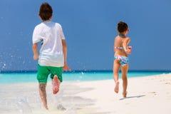 孩子获得乐趣在海滩 免版税库存照片
