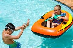 孩子获得乐趣在水池。 库存图片