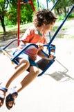 孩子获得在摇摆的乐趣 库存照片