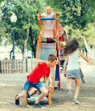 孩子获得在幻灯片的乐趣在操场 免版税库存图片