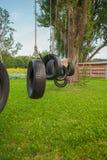 孩子获得握有父母的乐趣手在有轮胎来通过树的摇摆在前景和阳光的公园 ? 免版税库存图片