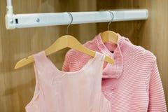 孩子行给垂悬在挂衣架穿衣 女孩的时尚 与孩子衣裳的衣橱 与桃红色的木挂衣架 库存照片