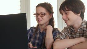 孩子观看事滑稽在膝上型计算机 库存照片