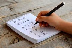 孩子解决数学例子 孩子在他的手上拿着一个黑标志 与乘法表例子的笔记本板料 免版税库存图片