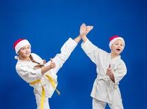 孩子训练反撞力腿并且显示超级的手指 库存图片
