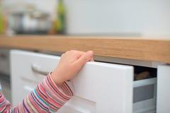 孩子设陷井在门的手指 免版税库存图片