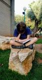 孩子读一本书坐石头 免版税库存照片
