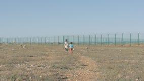 孩子走大约在难民营的土道路 概念移民危机贫穷的男孩和他的帮助的姐妹需要 股票录像