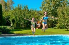孩子跳到游泳池水并且获得乐趣,孩子家庭度假 免版税图库摄影