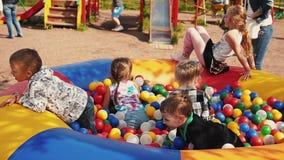 孩子跳并且使用对于儿童绷床充满颜色球 夏天Fest 股票视频