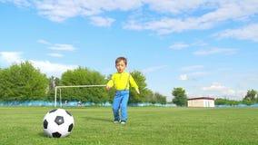 孩子踢在橄榄球目标的背景的一个足球 股票视频