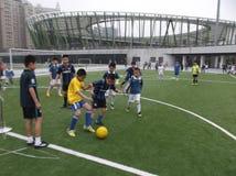 孩子踢橄榄球 库存照片