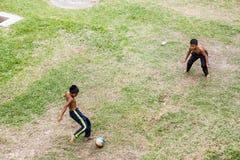 孩子踢橄榄球 库存图片