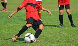 孩子踢足球 图库摄影