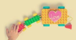 孩子递拉扯五颜六色的爱火车玩具块 图库摄影