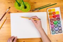 孩子递拿着在空白页,顶视图的一支铅笔 免版税图库摄影
