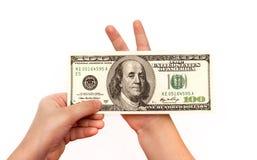 孩子递拿着100美元 免版税图库摄影