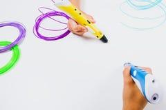 孩子递拿着3d与细丝的打印笔在白色背景 顶视图 库存照片