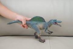 孩子递捉住在沙发的一个greu spinosaurus玩具 库存图片