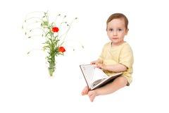 孩子通过书看为纪录 免版税库存图片