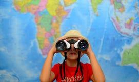 孩子通过双筒望远镜看  冒险和旅行概念 快乐的背景 库存照片