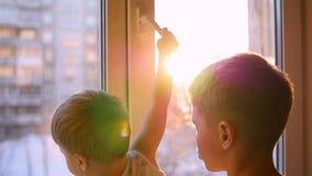 孩子通过在慢动作的太阳看窗口 股票录像