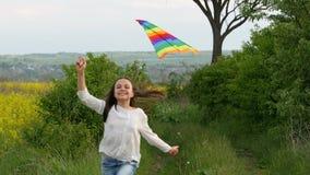 孩子通过有风筝的一个草甸跑 免版税库存照片