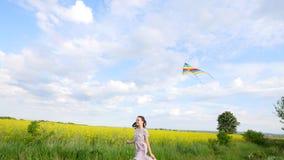 孩子通过有风筝的一个草甸跑 图库摄影