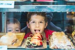 孩子通过玻璃在面包店 免版税库存照片